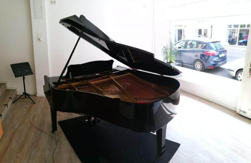 Der Flügel im Klavierstudio, hinter dem Schaufenster stehen Autos
