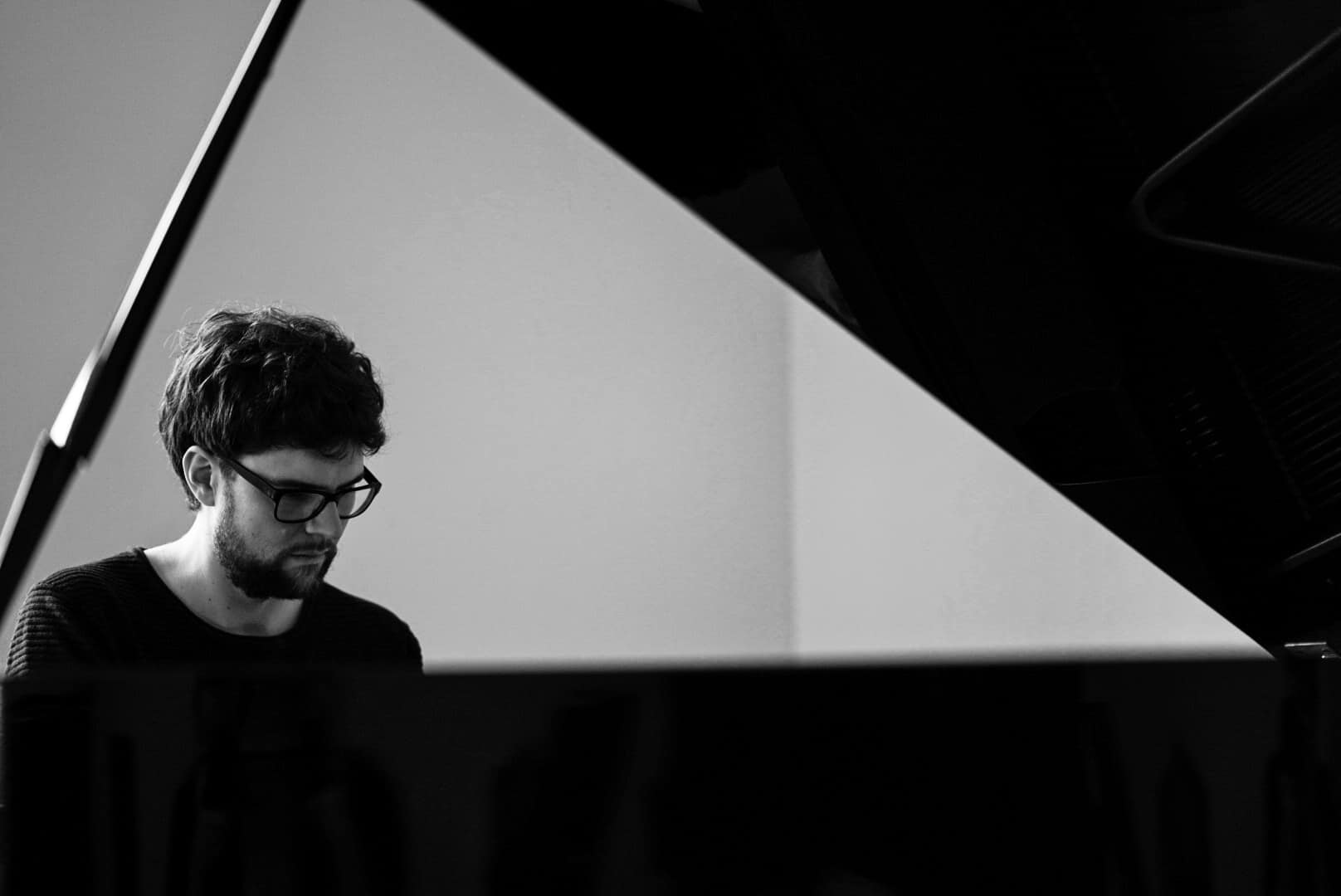 Blick auf den Pianisten Philipp Hermann durch den geöffneten Flügel hindurch