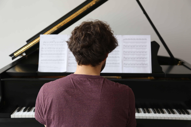 Pianist von hinten am Klavier