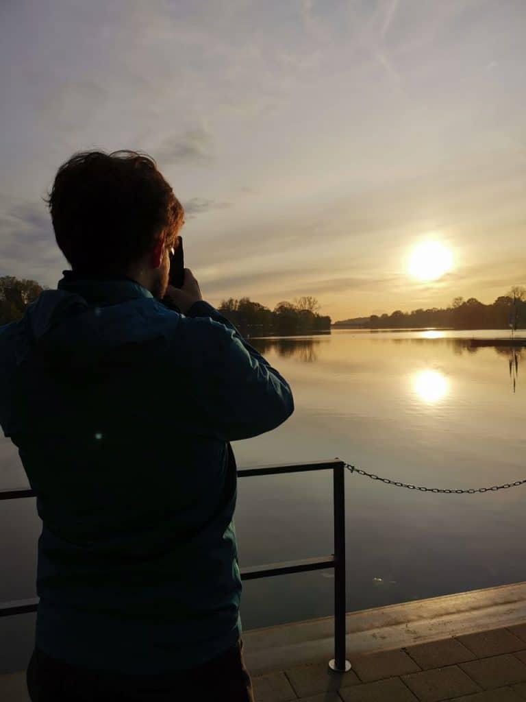 Philipp fotografiert den Sonnenuntergang über dem Aasee